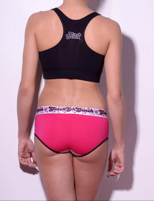 GG Ginch Gonch Mean Pink women's boy cut brief underwear, y front with pink and white panels and black trim with black, white, and pink printed waistband back shown with black sports bra