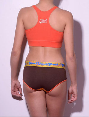 GG Ginch Gonch Lemon Heads women's underwear y front boy cut brief with yellow and brown panels, orange trim, and a printed yellow waistband. back. shown with orange sports bra.