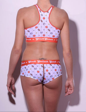 GG Ginch Gonch Hardball boy cut Brief cheeky gogo - women's Underwear - pin striped white fabric with basketballs, footballs, soccer balls, tennis balls, and baseballs. Orange trim with orange printed waistband back shown with matching sports bra