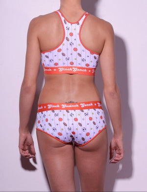 GG Ginch Gonch Hardball sports bra - women's Underwear - pin striped white fabric with basketballs, footballs, soccer balls, tennis balls, and baseballs. Orange trim with orange printed band back shown with matching briefs