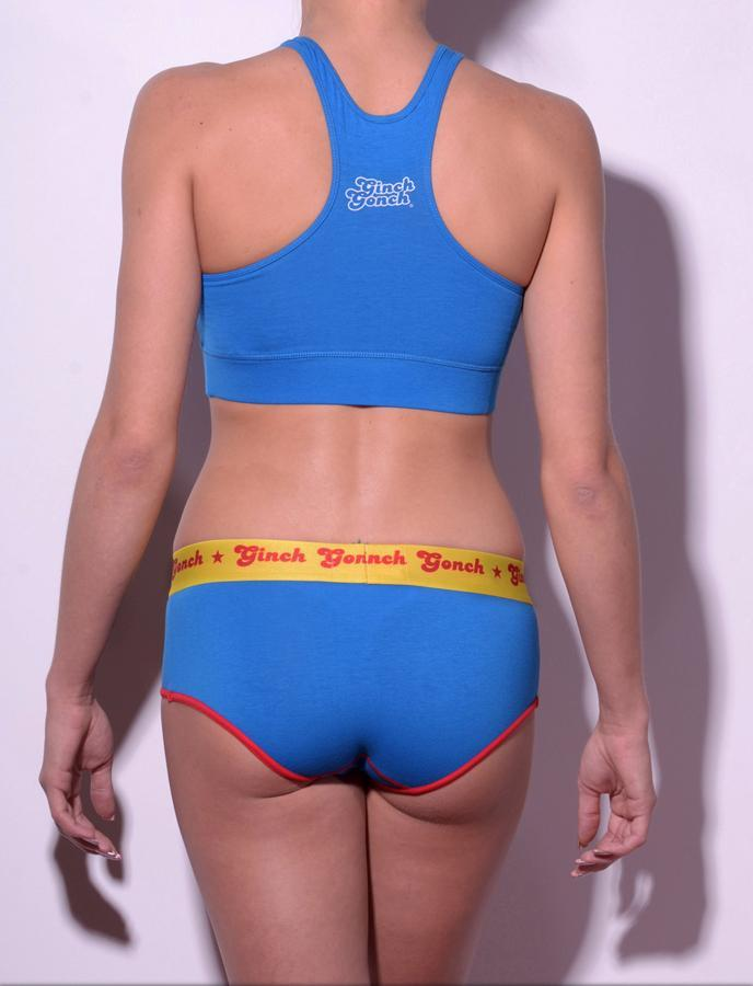 Ginch Gonch GG Ginchcredible super hero women's boy cut underwear brief blue fabric with GG logo, red trim, and yellow printed waistband shown with blue sports bra back