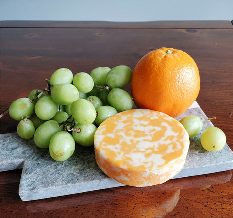 grapes, cheese, and a orange on a charcuterie board