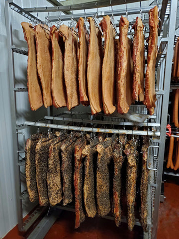 Original and pepper bacon slabs in the cooler after they have been smoked