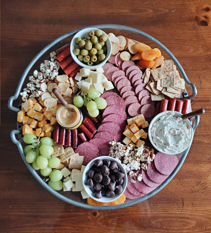 various fruits, crackers, meats, cheeses, olives, spreads, and wilbur buds on a charcuterie board