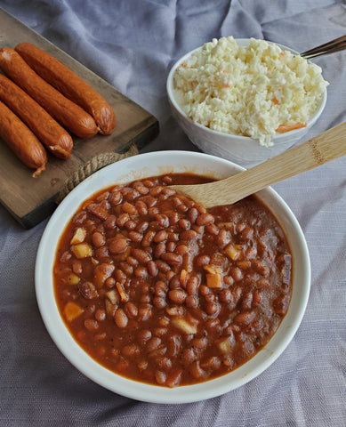 a full bowl of Slow Cooker Baked Beans with sausage links and a spread nearby
