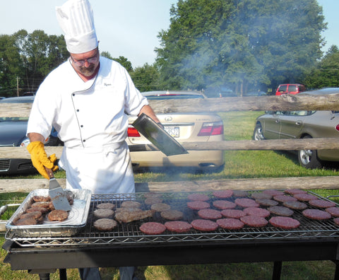 Stoltzfus Meats chef cooking burgers on a large grill