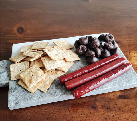 crackers, wilbur buds and honey BBQ snack sticks on a charcuterie board
