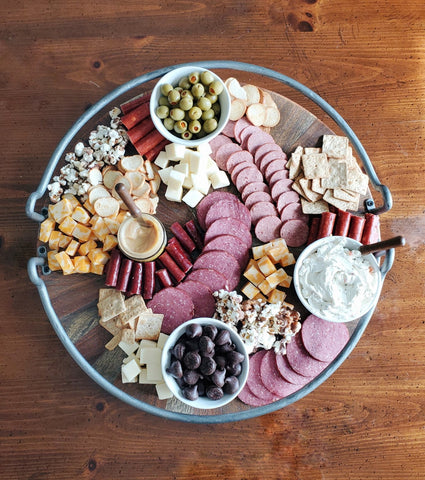 various crackers, meats, cheeses, olives, spreads, and wilbur buds on a charcuterie board