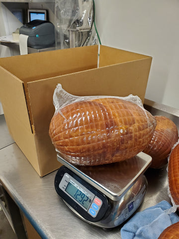 weighing fully cooled and packaged hams