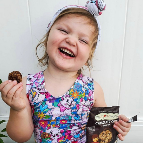 Left side text superfoods for superkids in navy blue and light green.  To the right is a female toddler, smiling with head tilted to the right and a floral wrap in her hair with a top knot. She is holding mysupersnack chocolate chip granola bites pouch.