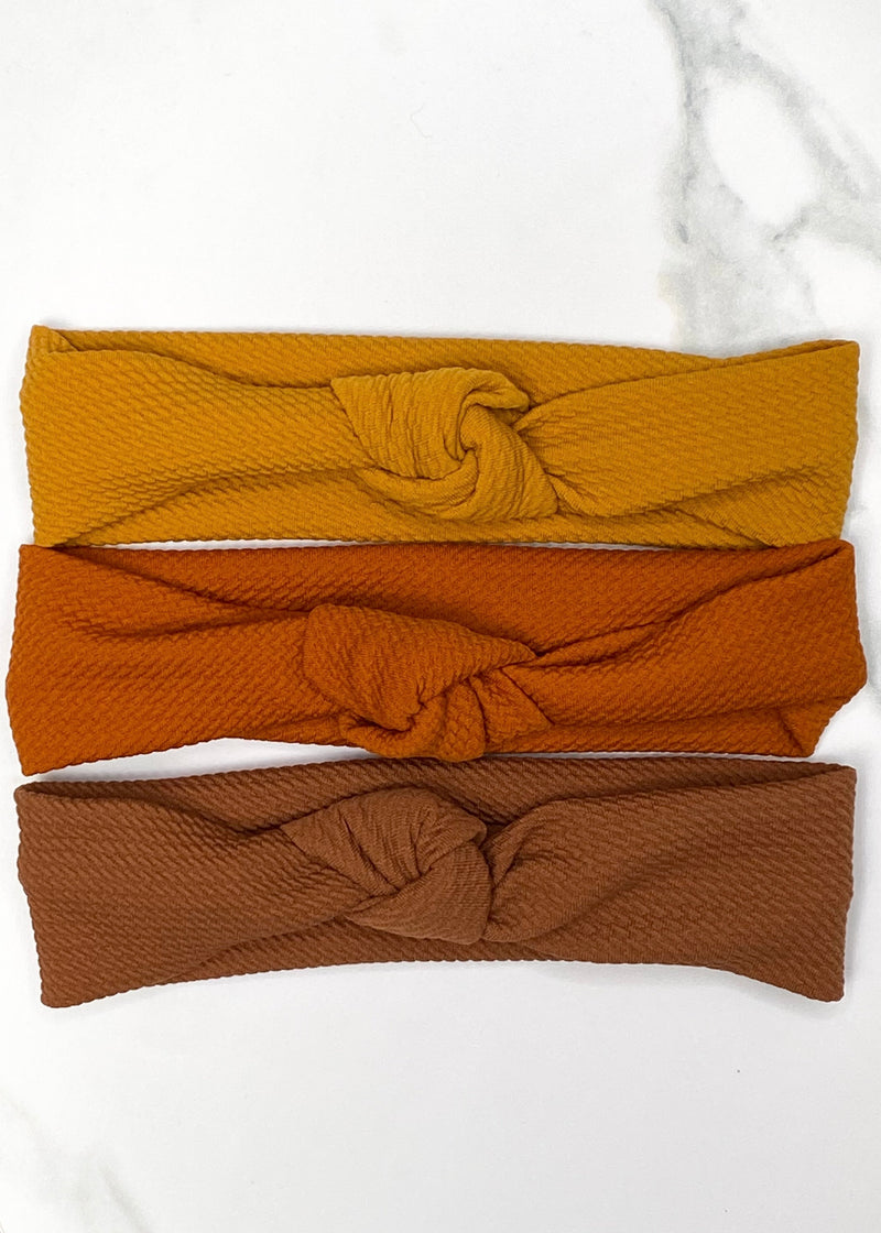 knotted baby headbands in burnt orange, mustard yellow, and brown.