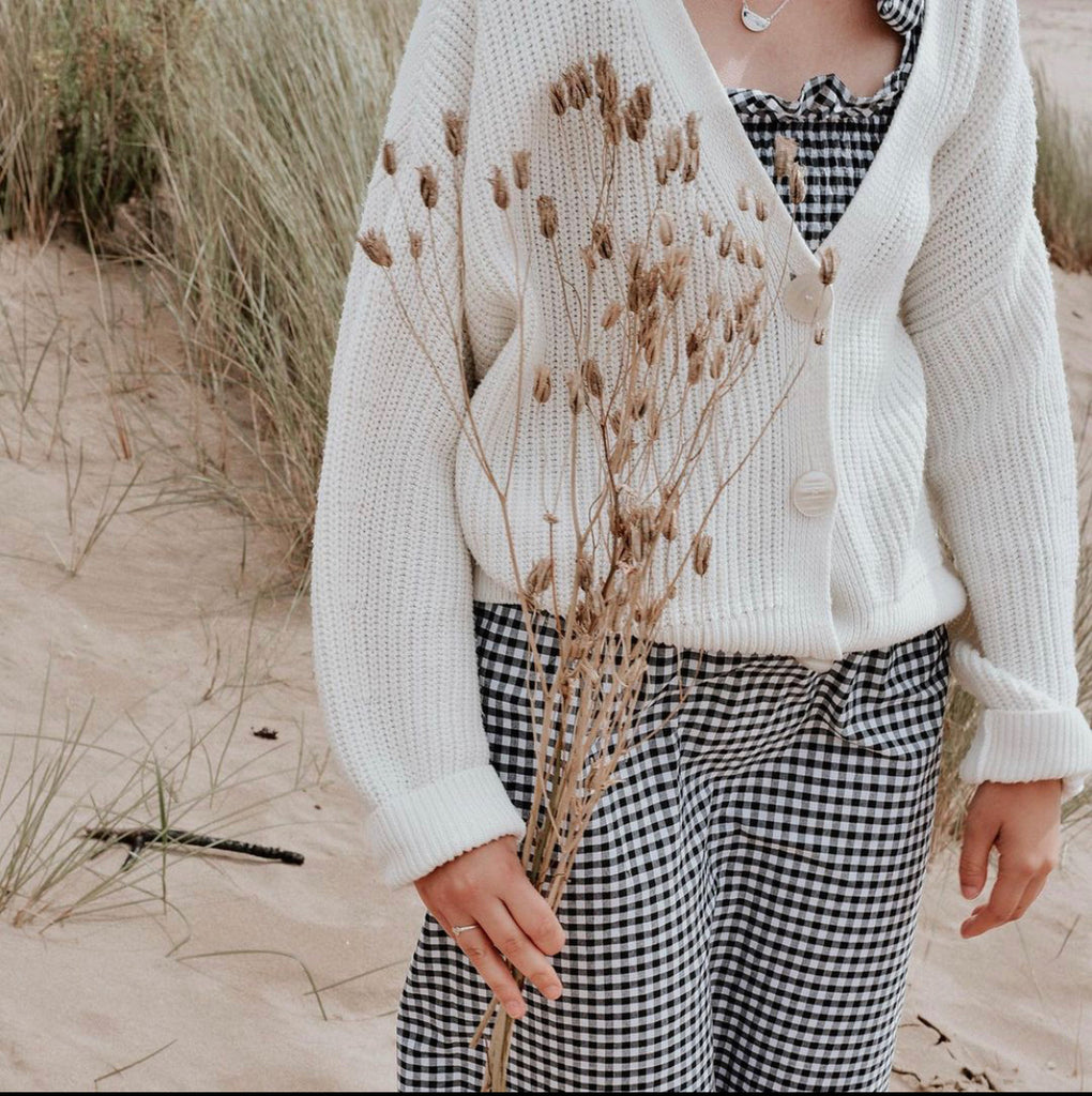 girl wearing gingham dress and cardigan in sand dunes