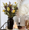 Gorgeous tabletop display of fresh flowers beside a vase of bleached palms and spears