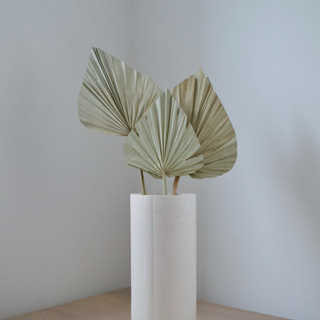 Tabletop display of a bunch of 3 natural coloured palm spears in simple, white vase