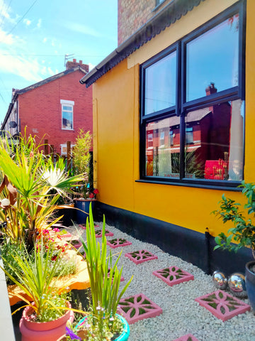 exterior of 70s house manchester 70s retro location home for film and tv and fashion, yellow outside with pink breeze blocks palm springs vibe