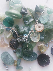 Ancient glass necklace on top of other pieces of ancient glass.