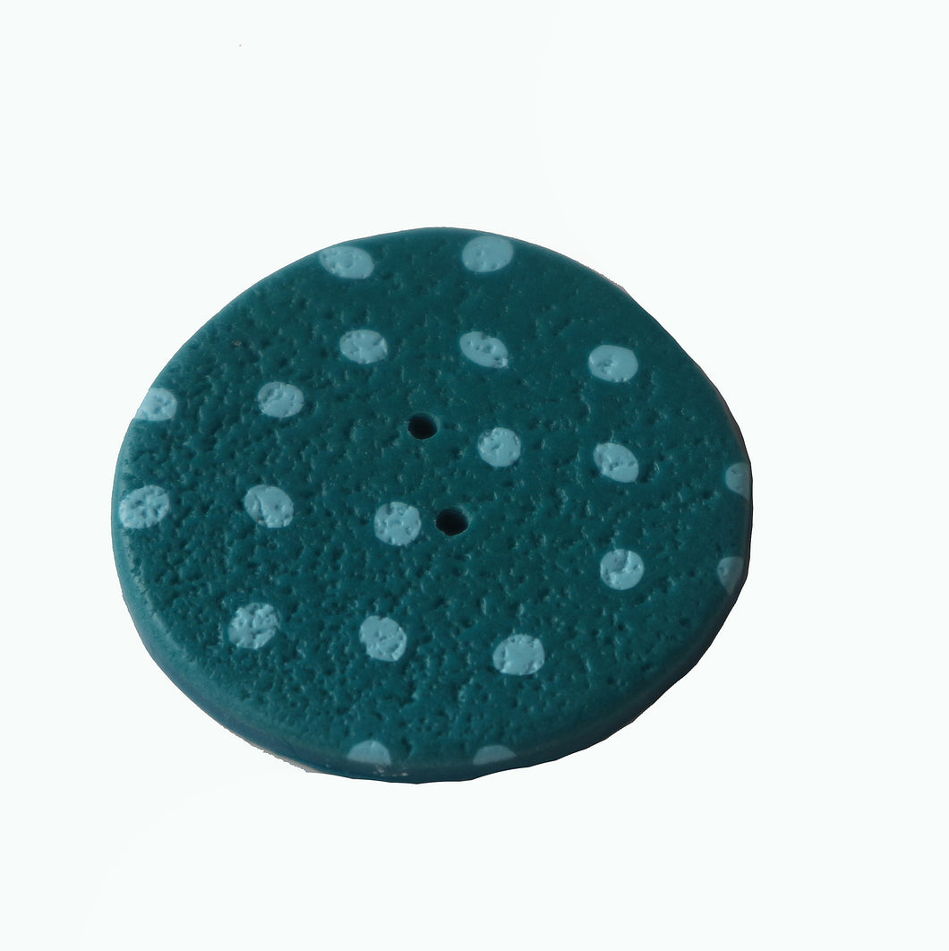 green round button with pale blue dots
