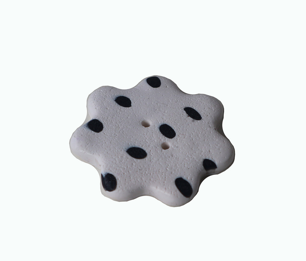 white flower shaped button with black dots