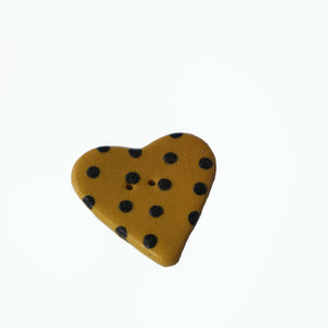 yellow heart shaped button with black dots