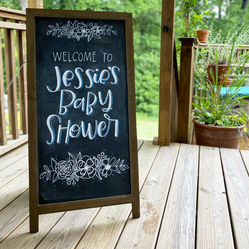 Stand up easel  chalkboard sign. At the top and bottom are handdrawn flowers in white. In the middle there is hand lettering that says