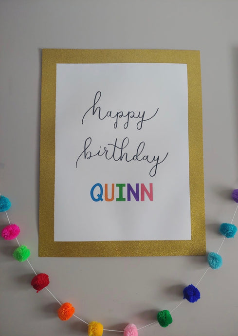 "This vertical poster is hand-lettered ""happy birthday"" in bouncy style black font calligraphy that can be customized with the name of the birthday gal or guy in coloured block lettering with gold poster banner."