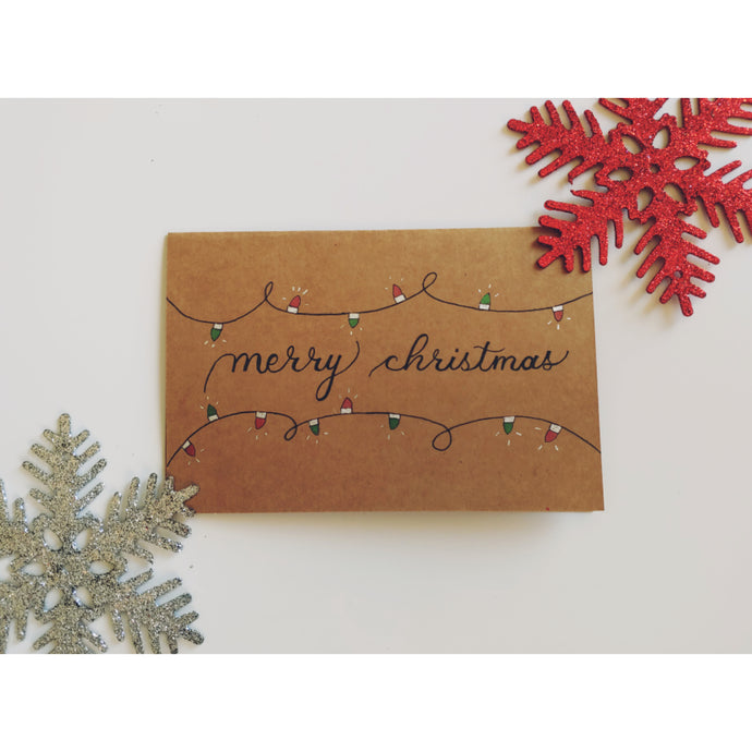 Merry Christmas card written in black calligraphy font with colourful Christmas lights with chrome accents