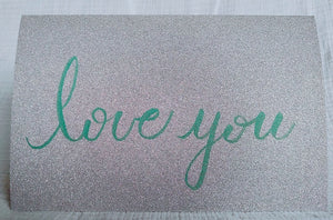 "Silver glitter cardstock card ""love you"" written in green brush pen"