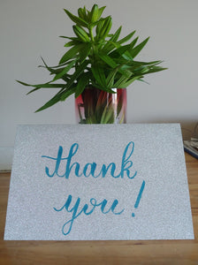 "Silver glitter cardstock card ""thank you"" written in blue brush pen"