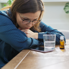 Woman looking at her phone with water and oils nearby, trying to figure out if she has estrogen dominance