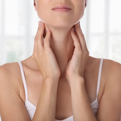Woman holding neck where thyroid is