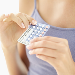 woman holding a pack of hormonal birth control