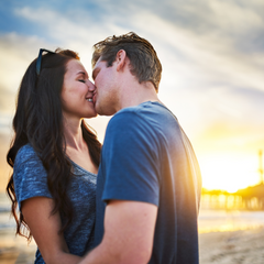 Couple kissing on the beach in the sunset