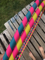 weighted hula hoops taped in turquoise and yellow pictured on a deck
