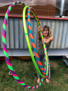 Woman holding 3 hula hoops, one beginner 3 colour hula hoop, one lime green hula hoop and one neon orange and teal small hula hoop all made for adults in nz