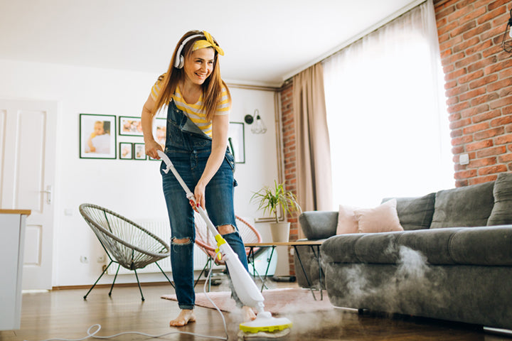 Woman cleaning house with headphones