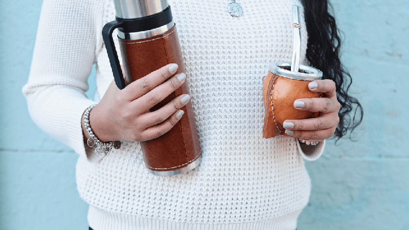Person Holding Thermos and Cup