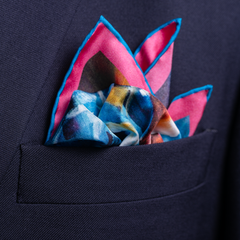Cycle road racing silk pocket square by Otway & Orford, Break Away, folded in top pocket. Made & hand-sewn in England in collaboration with 'painter of speed' John Ketchell