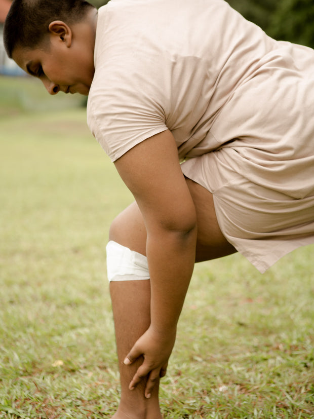 a woman wearing kneeheat while stretching on a field