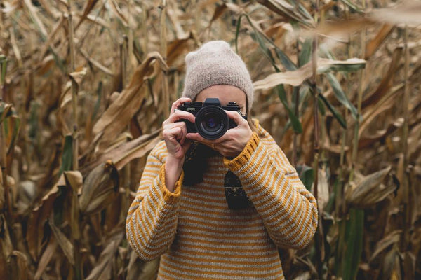 woman taking a picture wearing a yellow wool jumper