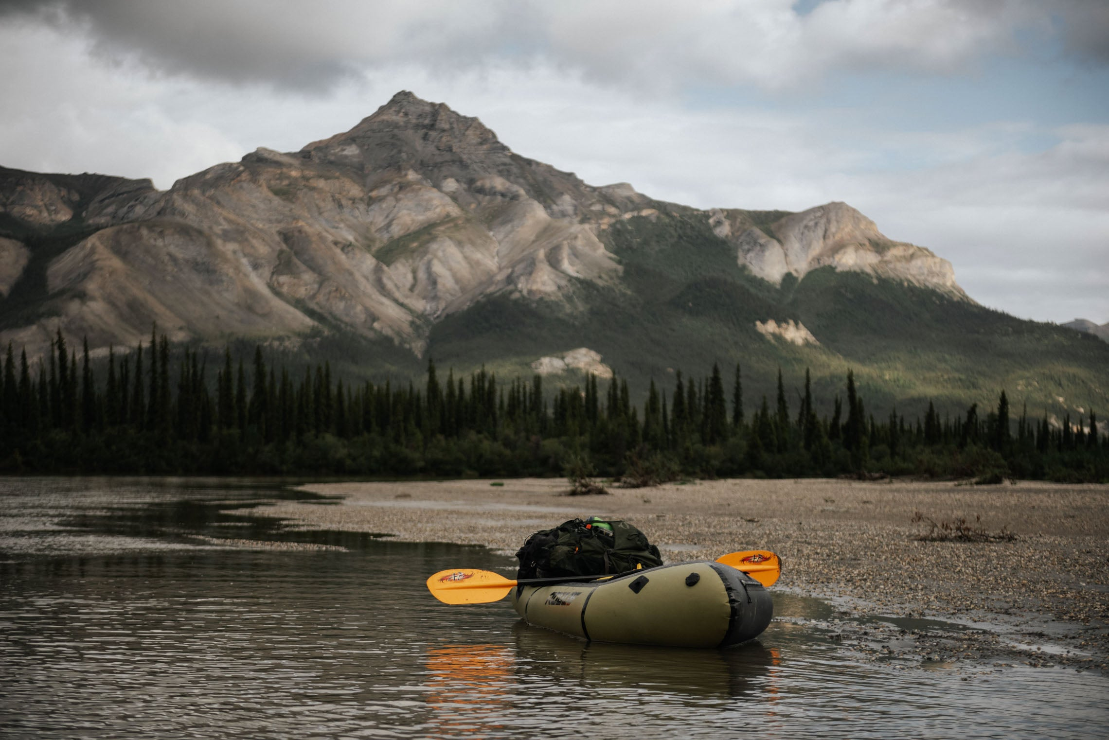 Packraft at the shore with arctic mountain in background