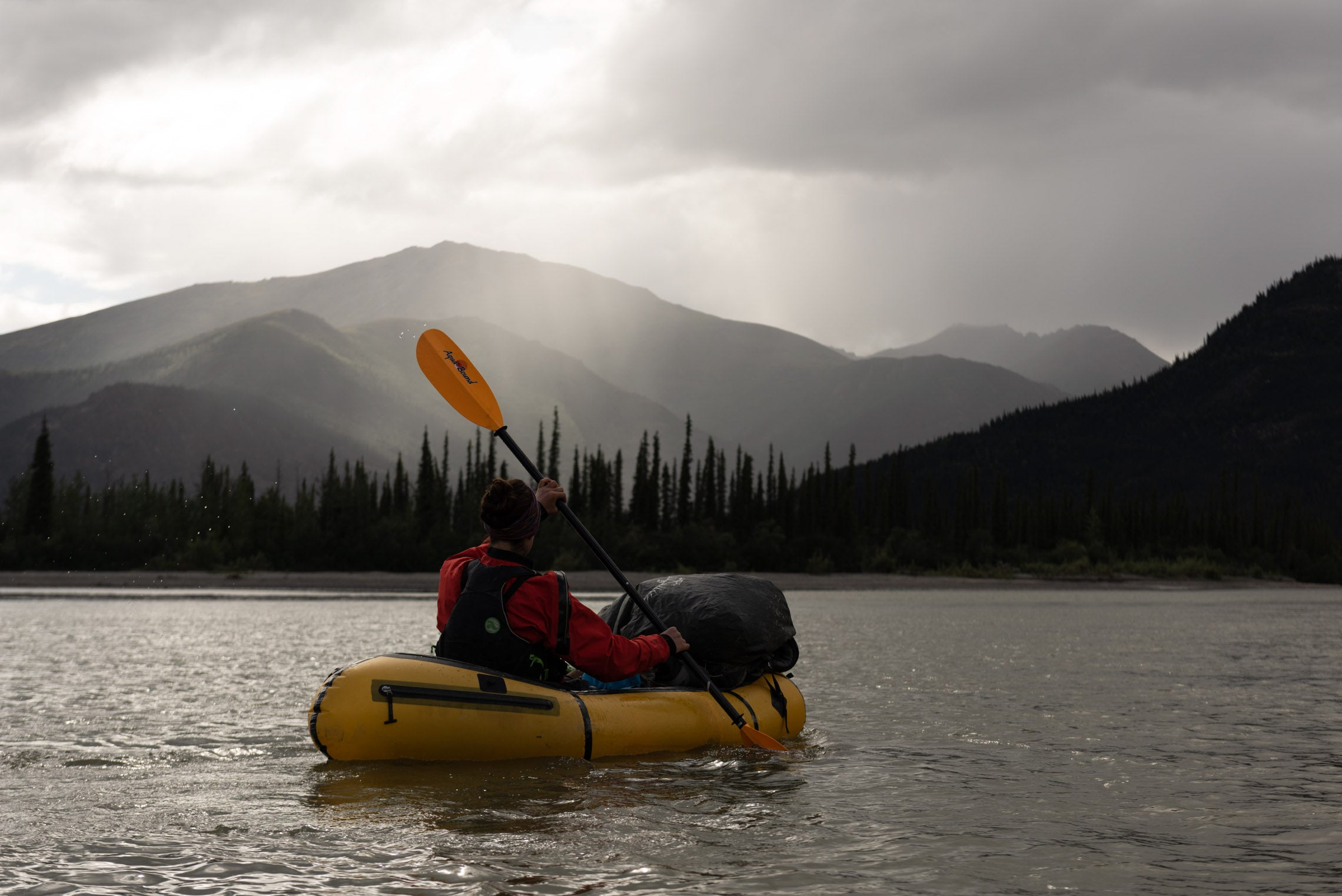 Person packrafting with gear in a lake with a mountain in the background