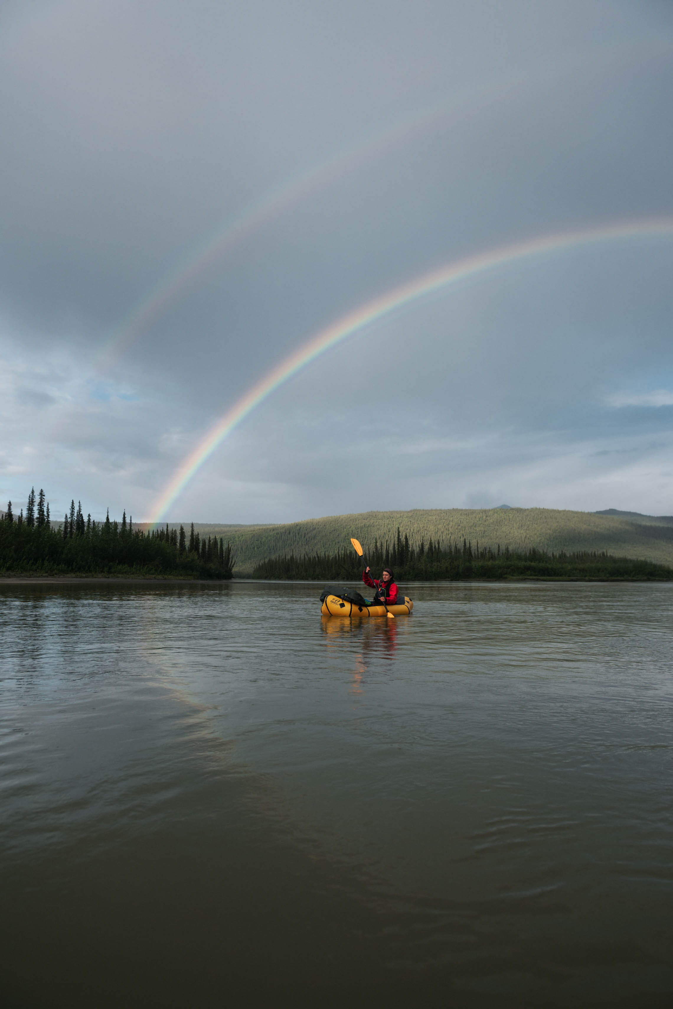 Person packrafting in an arctic lake with a double rainbow above
