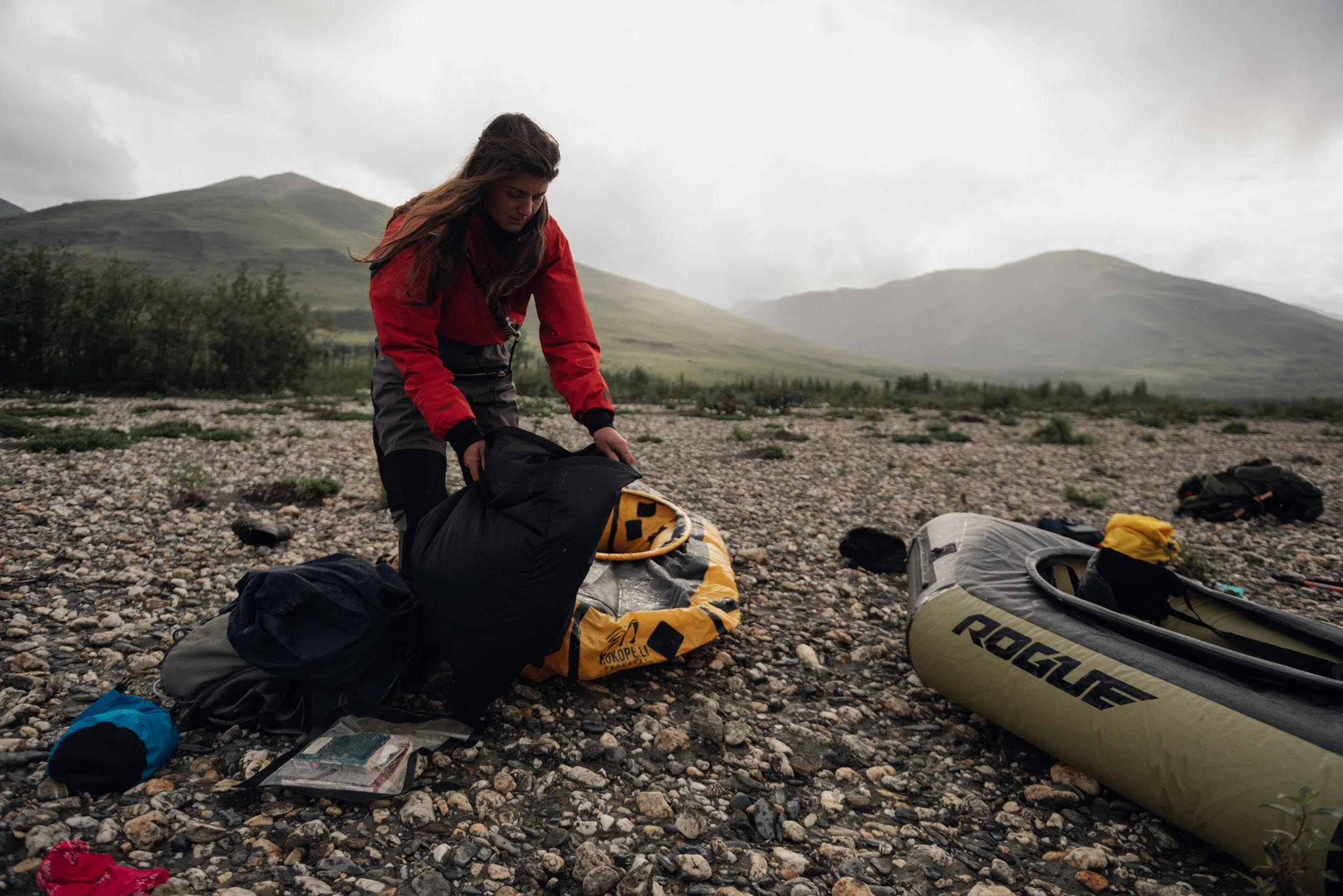 Woman packing a Kokopelli packraft in the gates of the arctic