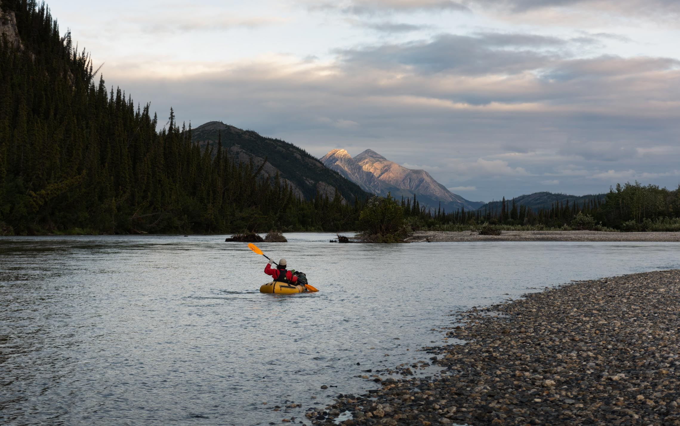 Packrafting in a lake at dawn with a snow capped mountain in the background