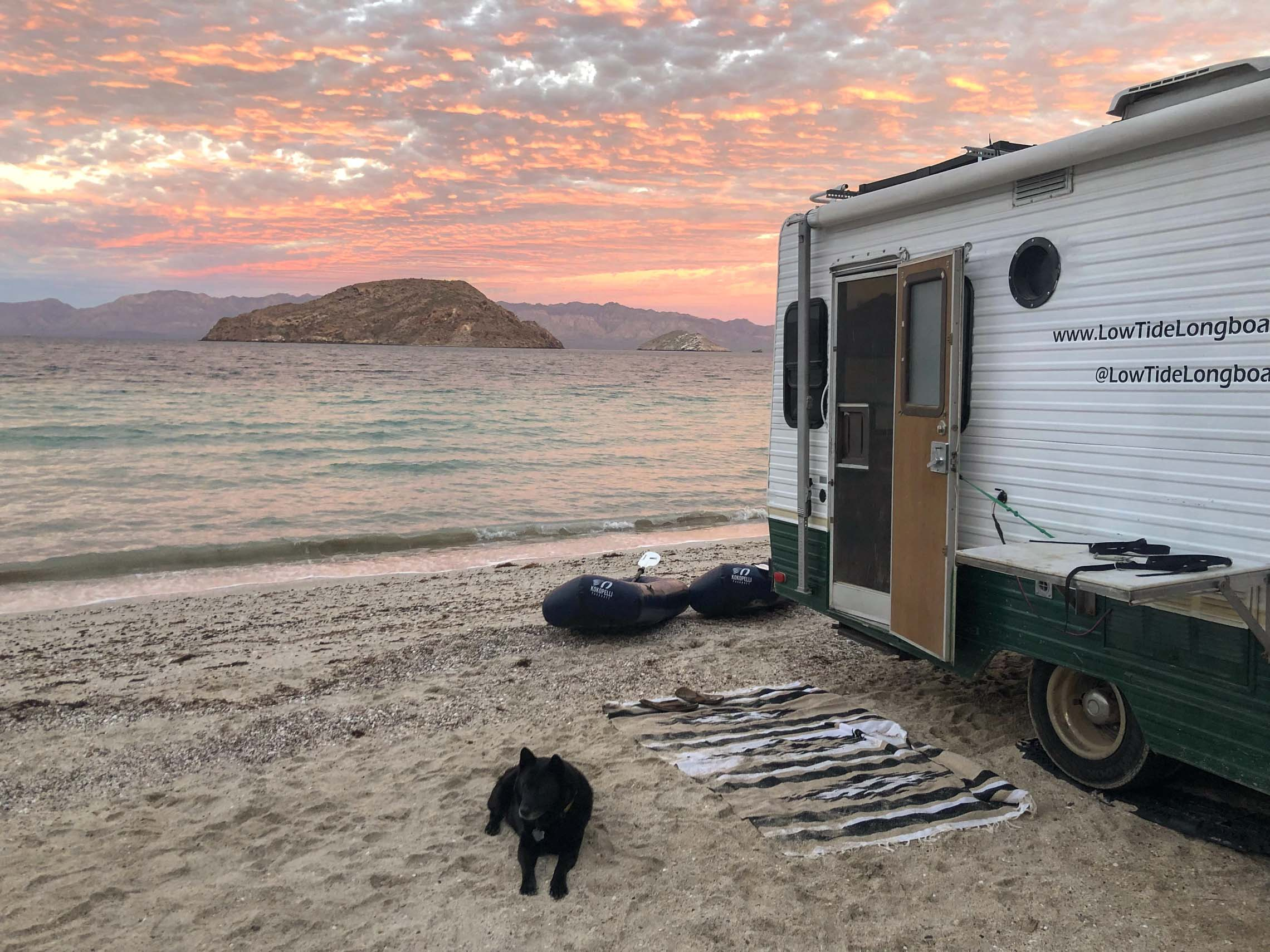 Dog laying down next to a van by a lake. Why the Hornet Life Kokopelli Packraft is for you