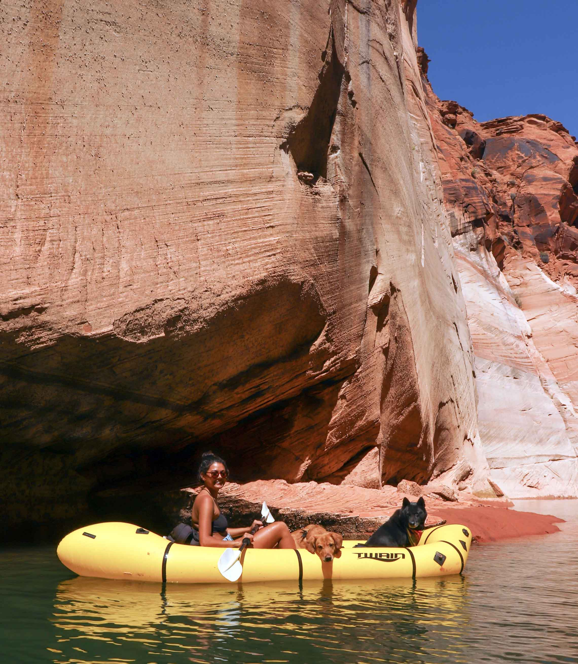 Woman and dog in a packraft next to a boulder. Vanlife to packrafting put-ins