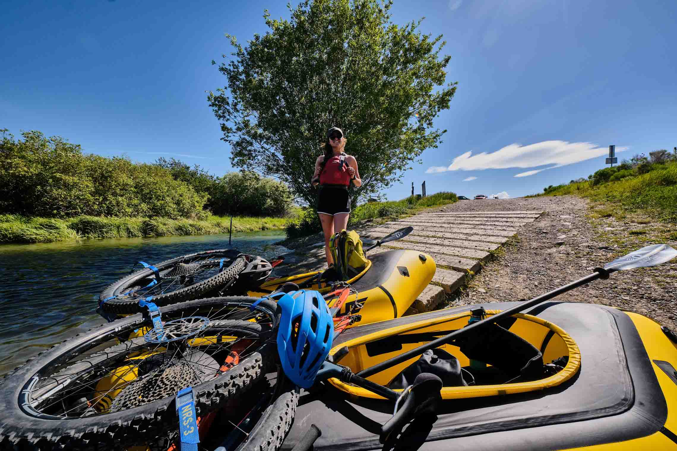 Bikes packed on packrafts next to water with a woman standing near them smiling