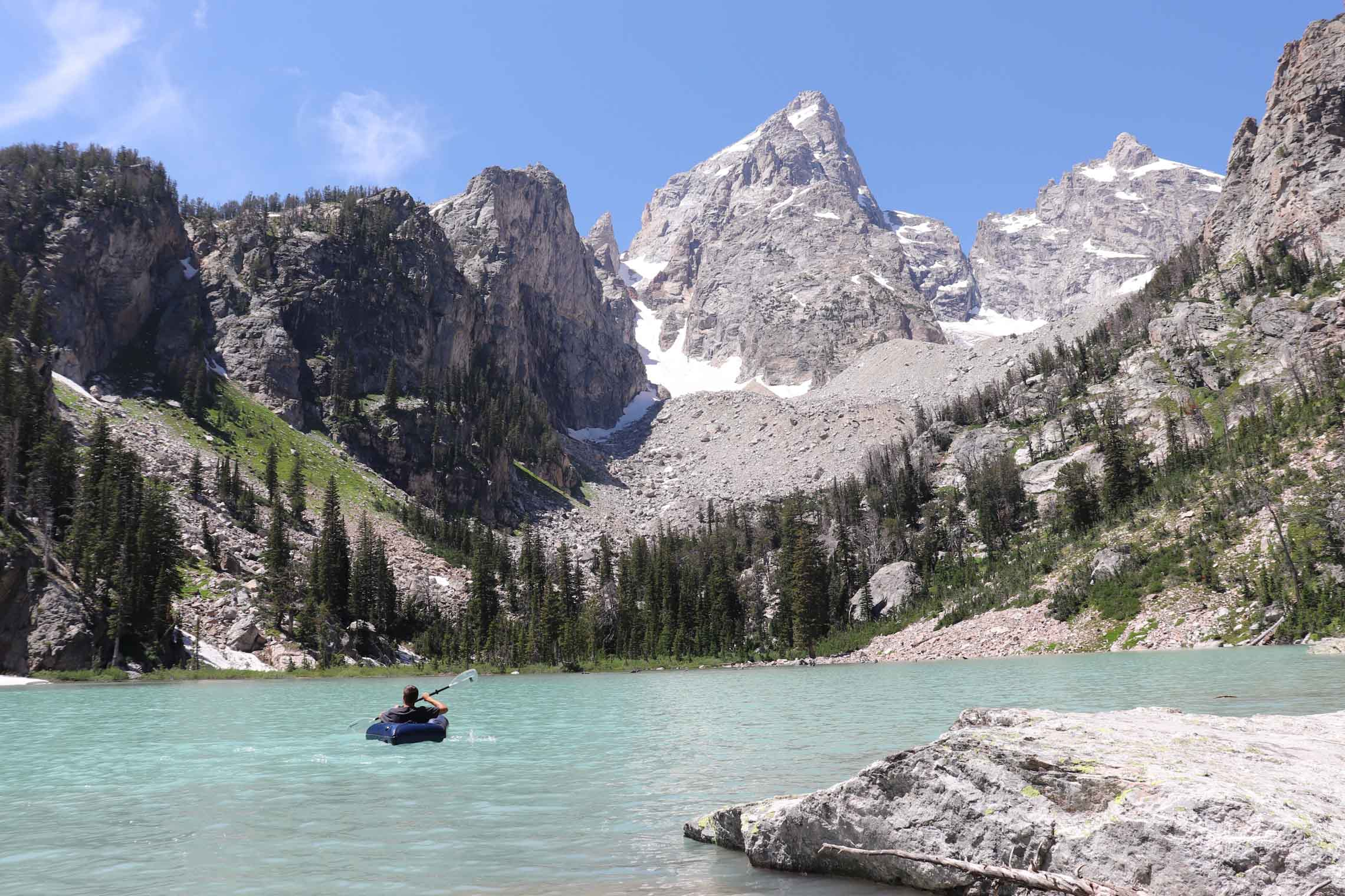 Man packrafting on crystal clear water with snow capped mountains in the background