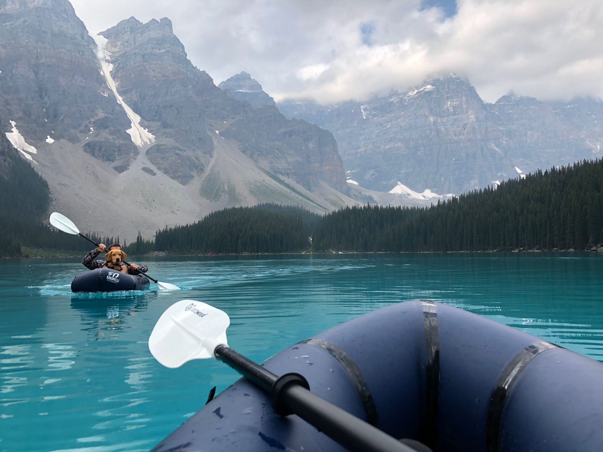 front of a packraft floating on clear water looking out to snow capped mountains and another packraft with a dog and a man in it