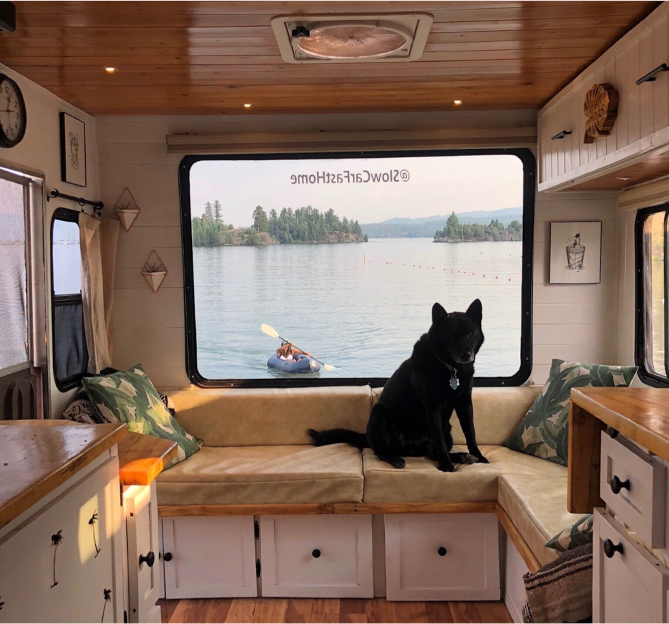 dog sitting in front of a van window looking out a packraft on a lake